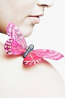 Close-up of a butterfly perching on a young woman's shoulder (thumbnail)