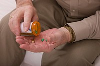 Senior man pouring pills from pill bottle, close_up of hands