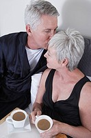 Mature couple having coffee in bed