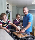 Girls baking with father in kitchen