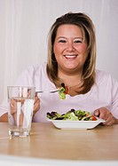 Portrait of smiling young woman eating salad