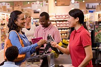 Mixed race woman paying with credit card in grocery store
