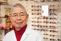 Chinese optician standing in store