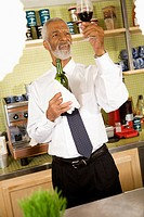 African business owner assessing glass of red wine