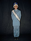 African boy wearing crown and pageant sash