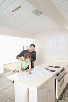 Couple in kitchen looking at blueprints