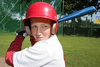 A boy in a baseball uniform holding a baseball bat
