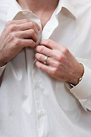 Midsection of a man unbuttoning a white shirt