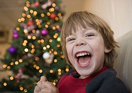 A young boy laughing in front of a Christmas tree