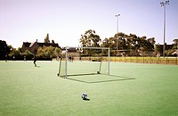 Soccer ball on soccer field with people training in background