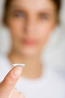 A woman holding a contact lens