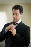 Mixed race man adjusting tie
