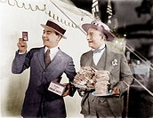 Man holding plates of sandwiches with a man looking at a film slide beside him Old Visuals