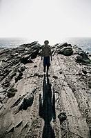 Boy Casting Shadow on Rocks