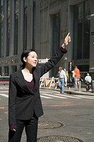 Young businesswoman standing on street hailing taxi