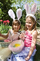 Two young girls sitting in garden with Easter baskets and wearing fluffy rabbit ears