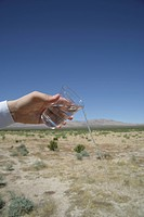 Businessman pouring water out of plastic cup in desert