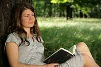 Young woman leaning against tree with a book
