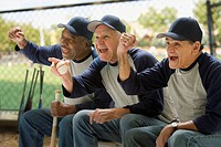 Baseball players cheering on bench