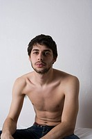 Young man sitting shirtless on bed