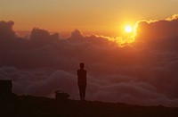 Person standing on a mountain ledge at sunrise