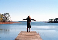 Young girl standing at the edge of a wooden jetty with her arms outstretched
