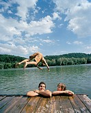 A young man diving into a lake with friends