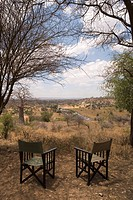 Two empty chairs overlooking African landscape
