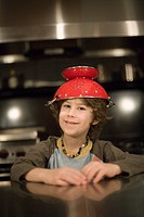 Young boy in a kitchen counter with a colander on his head