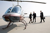 Businesswoman greeting two businessman by a helicopter