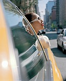 A woman leaning out of a taxi window, New York City, USA