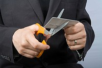 A businessman cutting up a credit card
