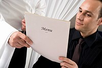 A waiter showing a man the menu