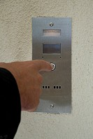 Detail of a man pressing an intercom button
