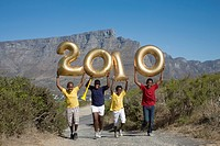 Jumping boys holding balloons shaped in numbers 2010, with South African flag, Table Mountain in background, Cape Town, Western Cape Province, South A...