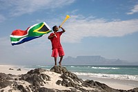 Young boy blowing on vuvuzela, while holding South African flag on beach, Table Mountain in background, Blouberg Beach, Cape Town, Western Cape Provin...