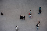 Two businessman looking up as people walk past