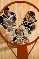 Three basketball players standing below a basketball hoop