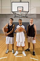Three basketball players standing on a basketball court