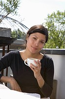 A young woman drinking coffee on a rooftop garden