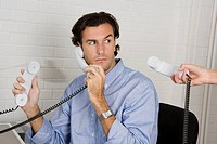 A businessman with three telephone receivers