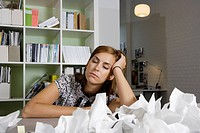 A woman sitting at a desk behind a pile of screwed up paper