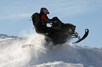 Man snowmobiling in mountains