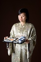 A woman in a kimono carrying a tray of sushi and tea