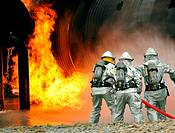 OFFUTT AIR FORCE BASE, Neb  – Offutt firefighters begin to extinguish the flames of simulated aircraft fire trainer during a joint training exercise  ...