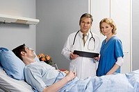 Two healthcare workers standing next to a patient in bed