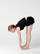 A young woman practicing the ´Upward Forward Fold´ yoga pose