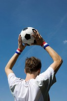 A soccer player throwing a soccer ball