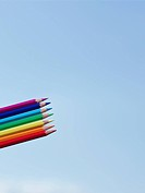 A rainbow of colored pencils against a blue sky