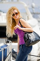 Attractive young woman with spectacles and big purse is boarding a yacht